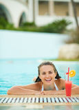 Happy young woman relaxing in pool with cocktail Royalty Free Stock Photography
