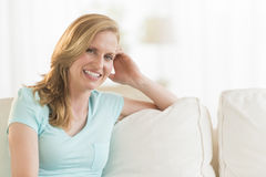 Happy Young Woman Relaxing On Sofa Royalty Free Stock Photo