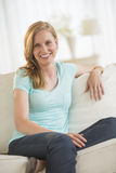 Happy Young Woman Relaxing On Sofa Stock Photos