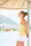 Happy young woman relaxing under beach umbrella Royalty Free Stock Images