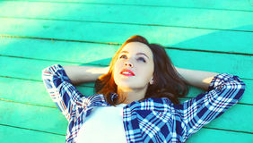 Happy young woman resting lying on a wooden floor Royalty Free Stock Photo