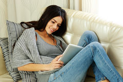 Happy young woman resting on a sofa with tablet computer Stock Image