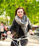 Happy young woman riding bicycle in green city park. Happy young woman riding a bicycle in the green city park Stock Photos