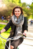 Happy young woman riding bicycle in  green city park. Happy young woman riding a bicycle in the green city park Stock Photo