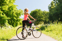 Happy young woman riding bicycle outdoors. Fitness, sport, people and healthy lifestyle concept - happy young woman riding bicycle outdoors stock photo
