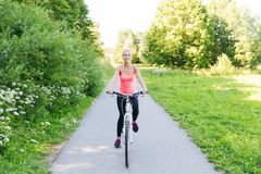 Happy young woman riding bicycle outdoors Stock Photo