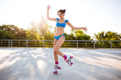 Happy young woman riding on roller skates outdoors Stock Photography