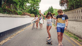 Happy young woman riding on skate with her friends Stock Images
