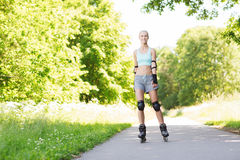 Happy young woman in rollerblades riding outdoors Stock Image