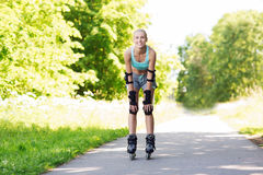 Happy young woman in rollerblades riding outdoors Stock Images