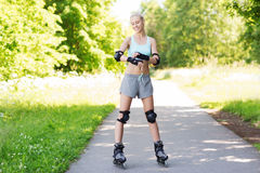 Happy young woman in rollerblades riding outdoors Stock Photo
