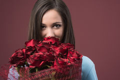 Happy young woman with roses. Happy young woman holding a beautiful red roses bouquet Royalty Free Stock Photography