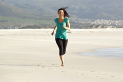 Happy young woman running along the sea shore Royalty Free Stock Photo