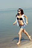 Happy young woman running on the beach Royalty Free Stock Photos