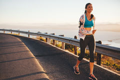 Happy young woman running on country road Royalty Free Stock Image