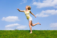 Happy young woman is running in a field. Against the backdrop of blue sky Royalty Free Stock Photography