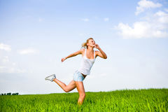 Happy young woman is running in a field Royalty Free Stock Images