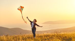 Happy young woman running with kite on glade at sunset in summer. Happy young woman running with a kite on a glade at sunset in summer Royalty Free Stock Image