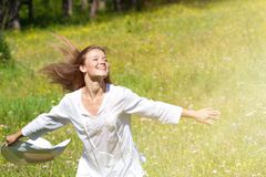 Happy Young Woman Enjoying Summer on the Green Meadow. Stock Photo