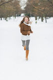 Happy young woman running in winter park Royalty Free Stock Images