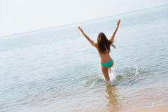 Happy young woman runs into the sea Stock Photography