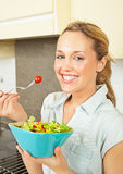 Happy young woman with salad. Pretty smiling young woman standing in the kitchen and holding a bowl with salad Stock Images