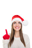 Happy young woman with Santa Claus hat pointing and looking up Royalty Free Stock Photo