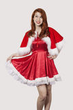 Happy young woman in Santa costume standing against gray background Royalty Free Stock Images