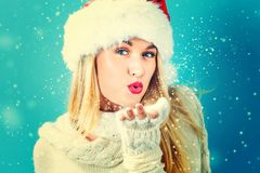 Happy young woman blowing snow. Happy young woman with Santa hat blowing snow Royalty Free Stock Photos