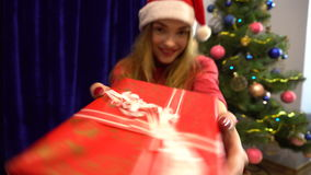 Happy young woman in santa hat dancing with christmas gift in hands stock footage