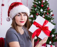 Happy young woman in santa hat with gift box near christmas tree Royalty Free Stock Images