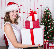 Happy young woman in santa hat with presents near Christmas tree Stock Photos