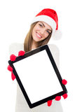 Happy young woman with Santa hat showing tablet computer Royalty Free Stock Images