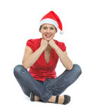 Happy young woman in Santa hat sitting on floor Royalty Free Stock Photo