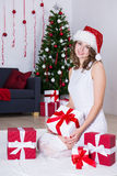 Happy young woman in santa hat sitting near decorated Christmas Stock Photos