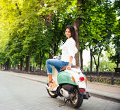 Happy young woman on a scooter Royalty Free Stock Images