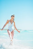 Happy young woman at seaside playing with water Royalty Free Stock Image