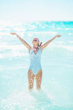 Happy young woman at seaside playing with water Royalty Free Stock Images