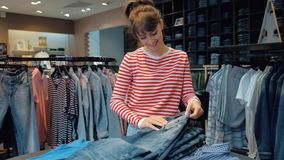 Happy young woman seller in denim boutique leafing through a stack of jeans stock video footage