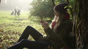 Happy young woman sending sms texting in the autumn park. stock video footage