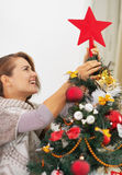 Happy young woman setting top on christmas tree Stock Image