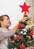 Happy young woman setting top on christmas tree Stock Image