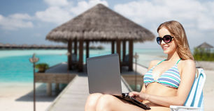 Happy young woman in shades with laptop on beach. Summer holidays, vacation, technology, people and internet - happy young woman in shades with laptop computer Royalty Free Stock Image