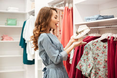 Happy young woman shopper in blue dress choosing clothes Royalty Free Stock Photos