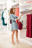 Happy young woman shopper in blue dress choosing clothes Royalty Free Stock Image