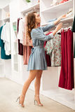 Happy young woman shopper in blue dress choosing clothes Royalty Free Stock Photography