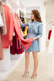 Happy young woman shopper in blue dress in shop Royalty Free Stock Images