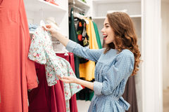 Happy young woman shopper in blue dress in shop. Image of happy young woman shopper in blue dress in shop choosing clothes. Looking aside stock photo