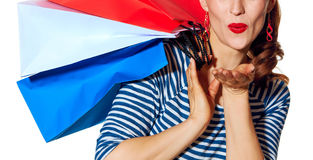 Happy young woman shopper on white background blowing air kiss. Shopping. The French way. Closeup on happy young woman with shopping bags of the colours of the Royalty Free Stock Images