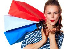 Happy young woman shopper on white background blowing air kiss. Shopping. The French way. Portrait of happy young woman with shopping bags of the colours of the Royalty Free Stock Photo